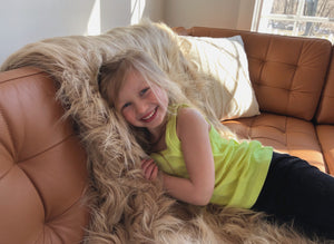 little girl snuggling with caramel brown faux fur throw in double sided fur on brown leather couch. Handmade in America by FuRmanity