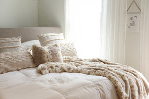 luxury neutral bedroom with light shining through window and faux fur animal print fabric pillow and blanket on bed