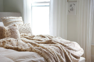 double sided, luxury, faux rabbit fur throw blanket and matching animal print pillow set on bed