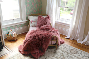 girls bedroom with luxurious faux fur pink blanket on bed with matching pillow