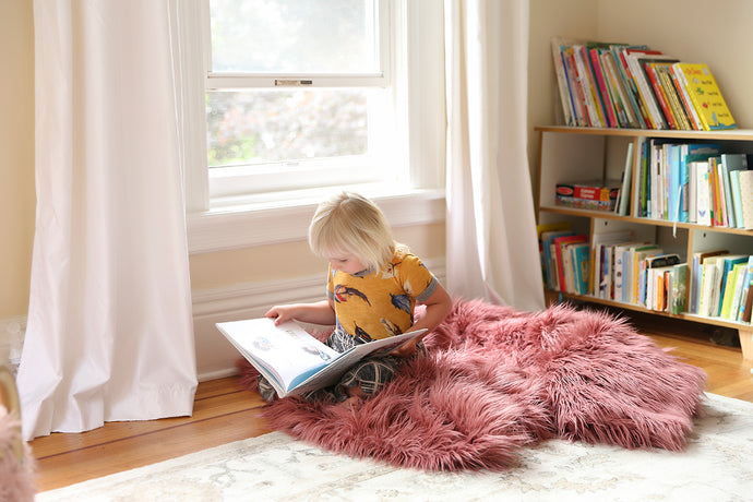girl sitting by window reading a book on our pink vegan faux fur blanket for kids
