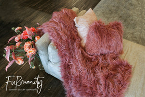 rose pink, long, thick faux fur blanket draped over chaise lounge with matching pillow and flowers