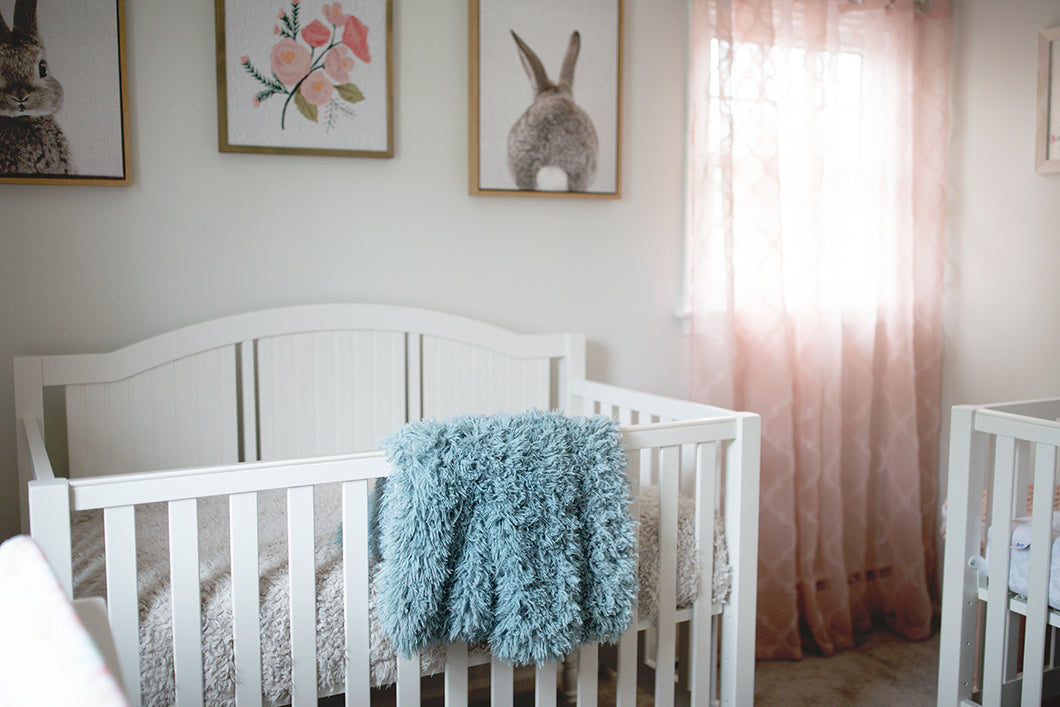 blue, green double sided, super warm and soft faux fur blanket in baby nursery, hanging over crib