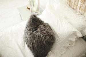 thick and plush, american made, dark gray faux fur pillow on bed