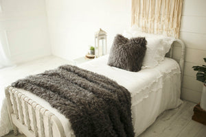 gorgeous, dark gray, handmade vegan faux fur pillow and throw on white bed