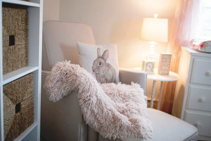 light peach luxury vegan fur throw in little girl's nursery room on chair with bunny pillow