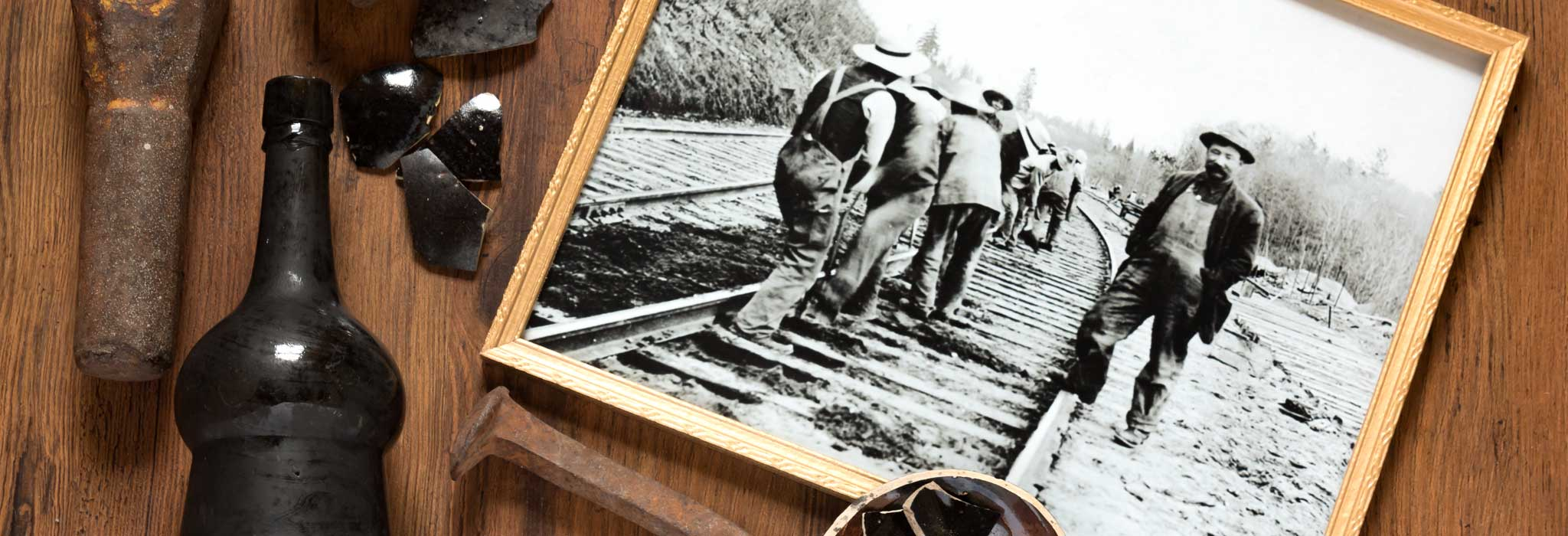 Black and white image of men working on railway tracks surrounded by artifacts