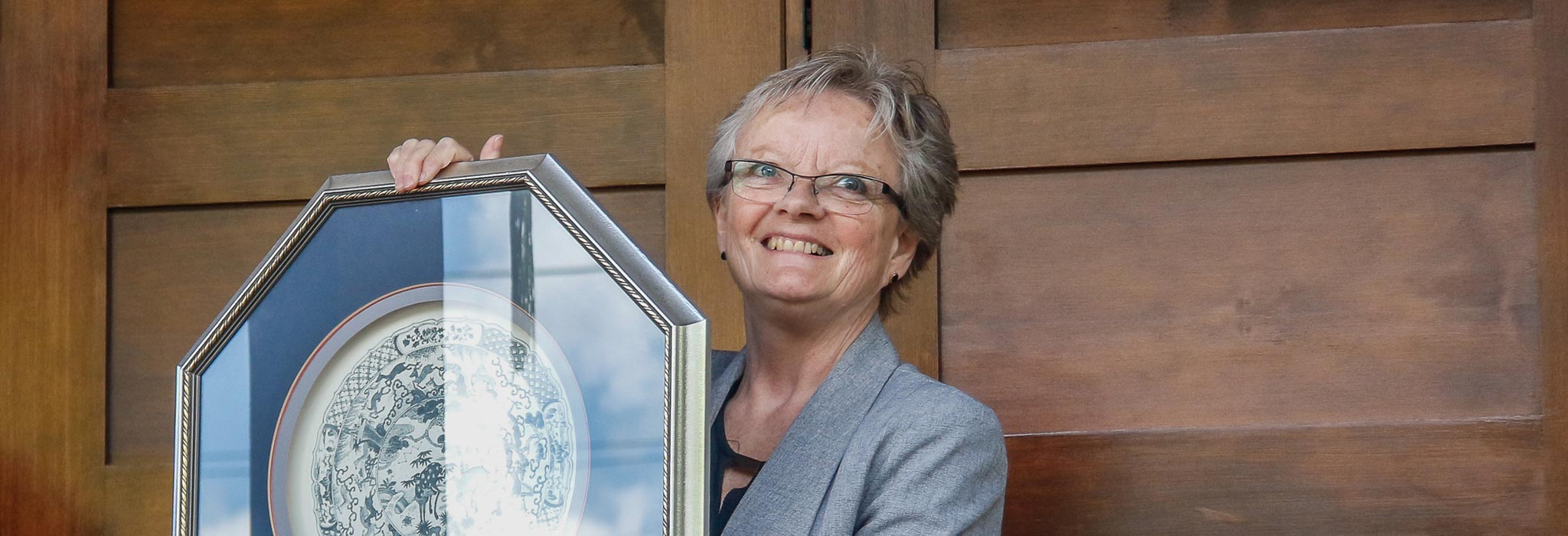 Lorna Fandrich holding a framed plate at the doors of the museum