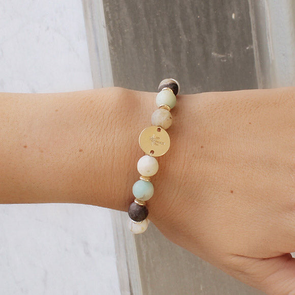 taudrey spa day beaded bracelet with white turquoise beads, cool jade tones and personalized gold charm detail