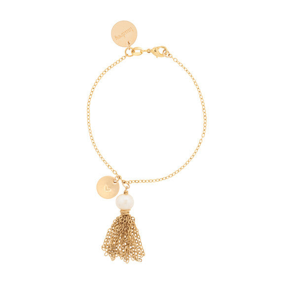 taudrey tassles on a gold leash bracelet with charm and gold tassel