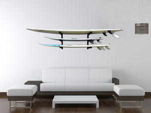 Wall mounted surfboard racks in house powder coated black to hold 3 surfboards