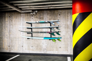 Wall mounted onto garage surfboard racks powder coated black to hold 4 surfboards or mal