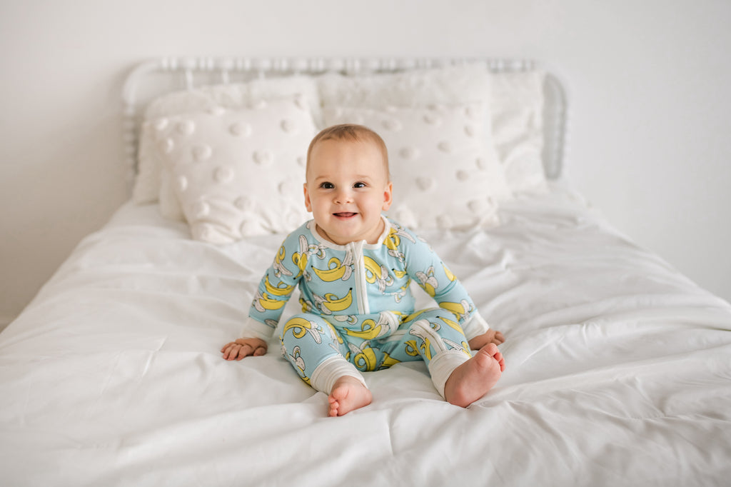 baby in banana pajamas sitting on a bed