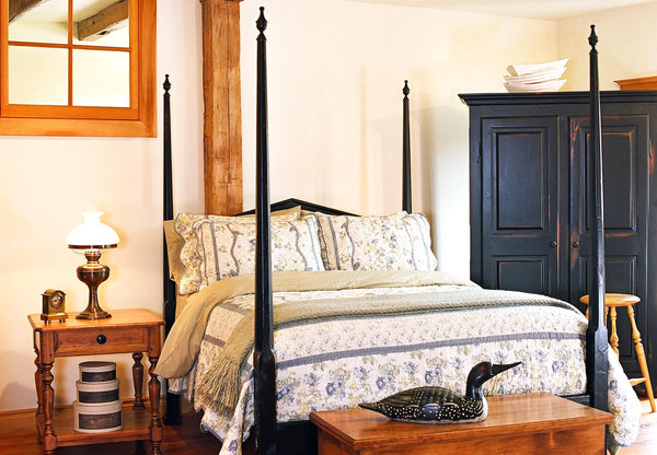 Pencil post bed with armoire and nightstand.