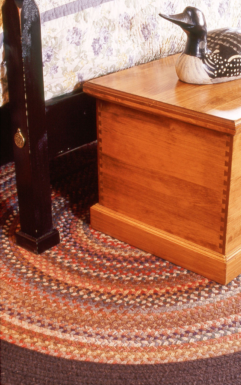 Pencil post bed, foot detail with blanket box and braided rug.