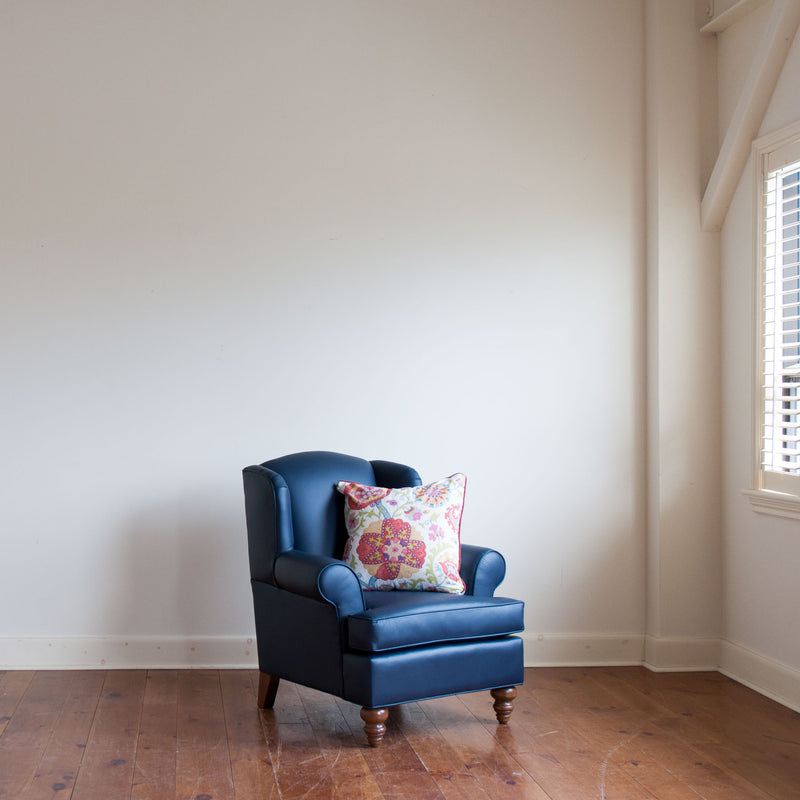Walmer wingback chair in navy leather with contrasting toss pillow, wide crop, angle view