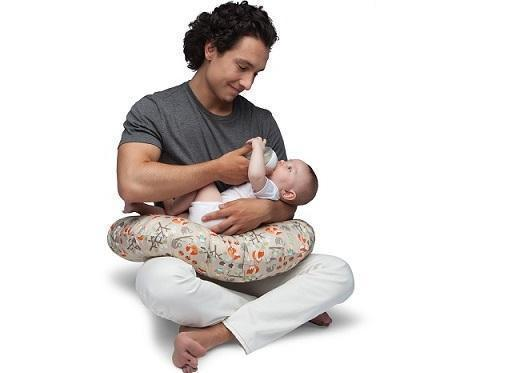 Dad bottle feeding baby using a Boppy Pillow