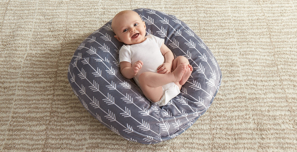 Baby laying in Boppy Newborn Lounger with Gray Arrows cover.