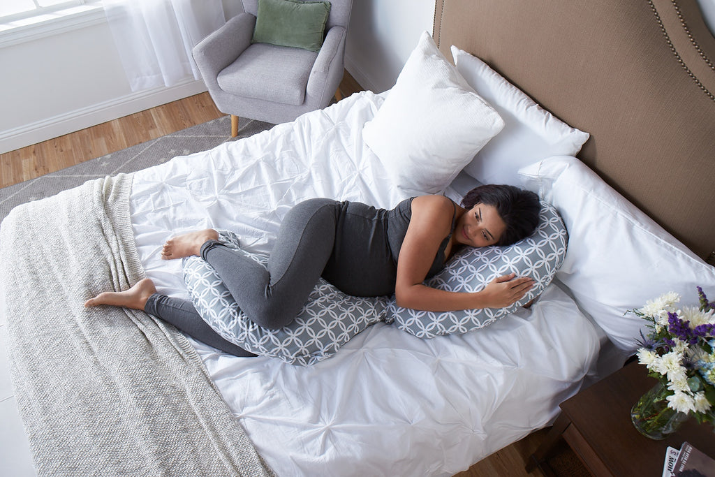 Woman laying in a bed with a pregnancy pillow