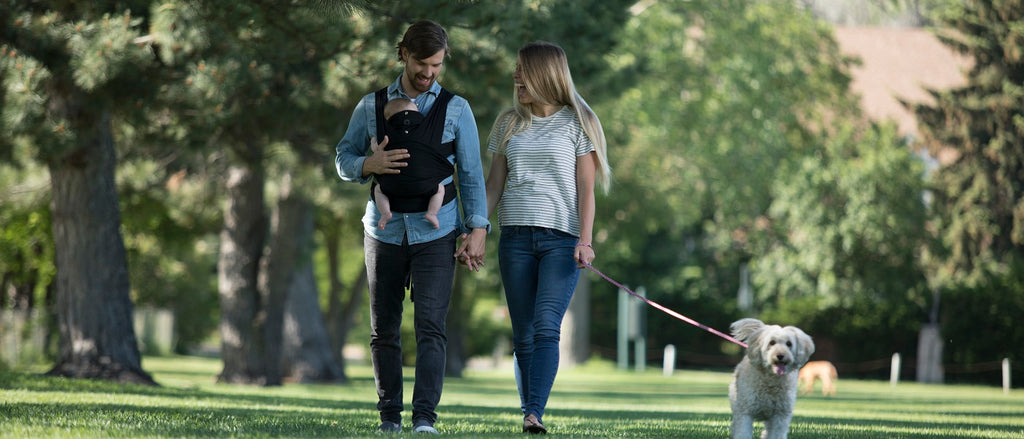 Family walking a dog with the dad wearing a baby carrier
