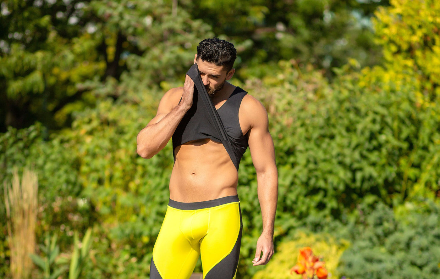 Man wearing black tank and yellow meggings
