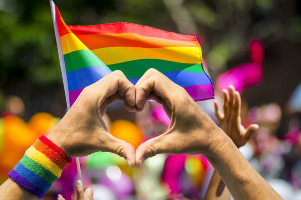 Man making a heart with his hand in front of a pride flag