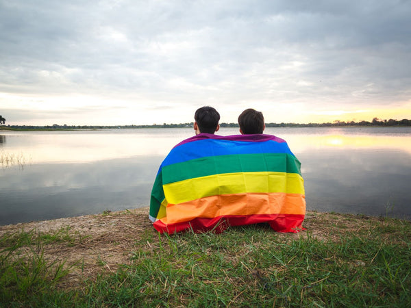 Two men sitting on the edge of a lake with a pride flag draped over their shoulders