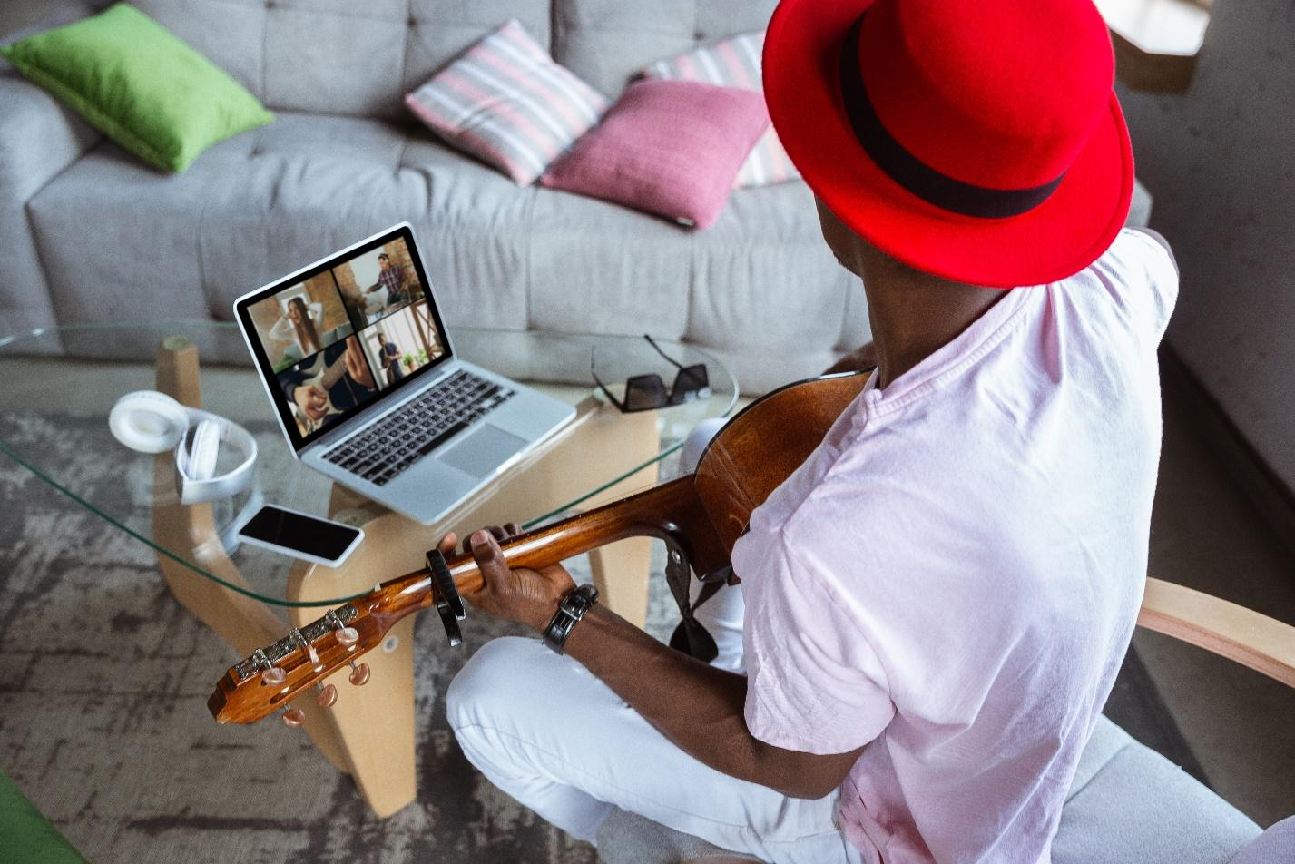 African-american musician playing guitar during online concert at home
