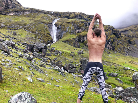male standing on the cliff in yoga pose