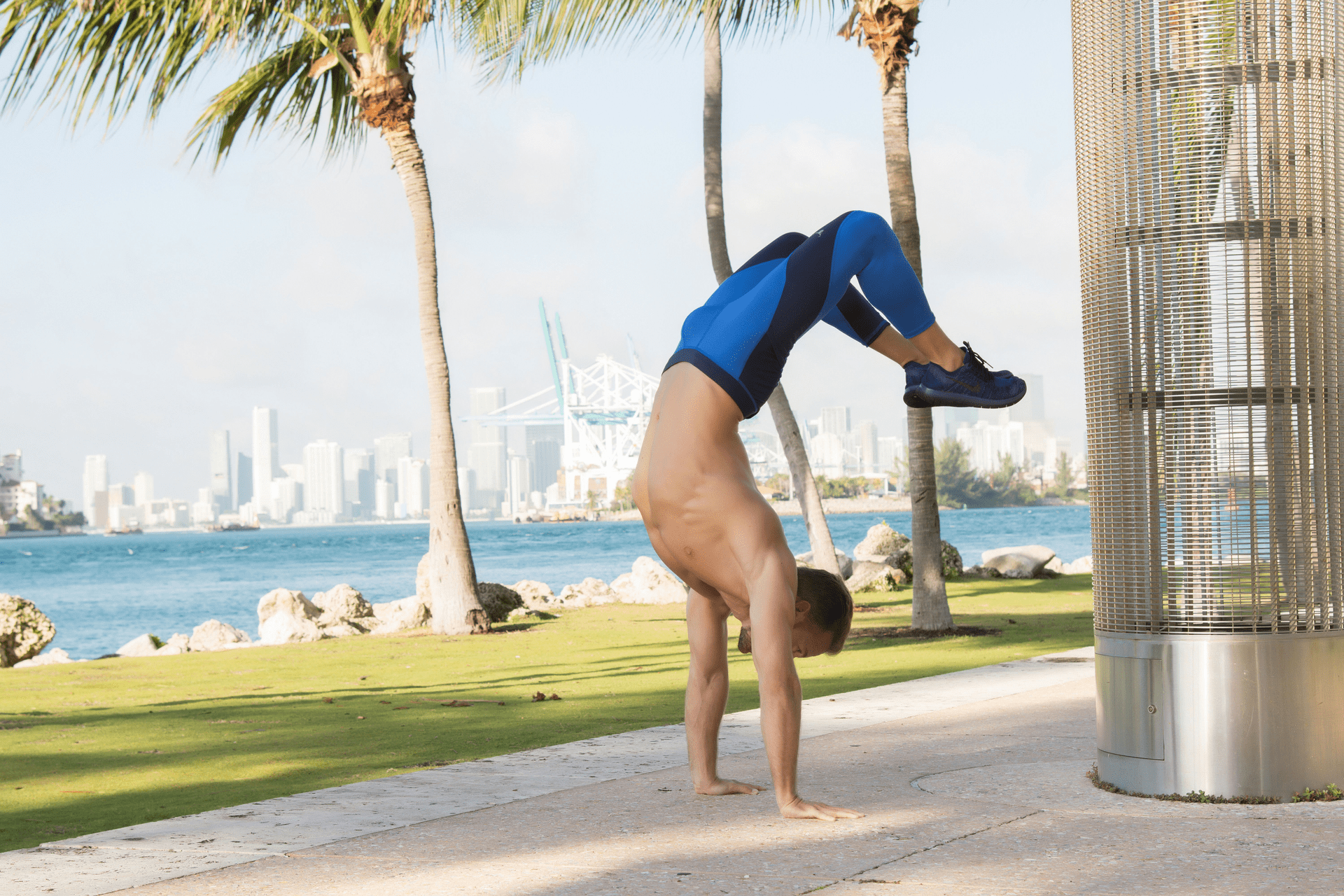 Valentine Aseyo Man performing handstand with river and skyline in background