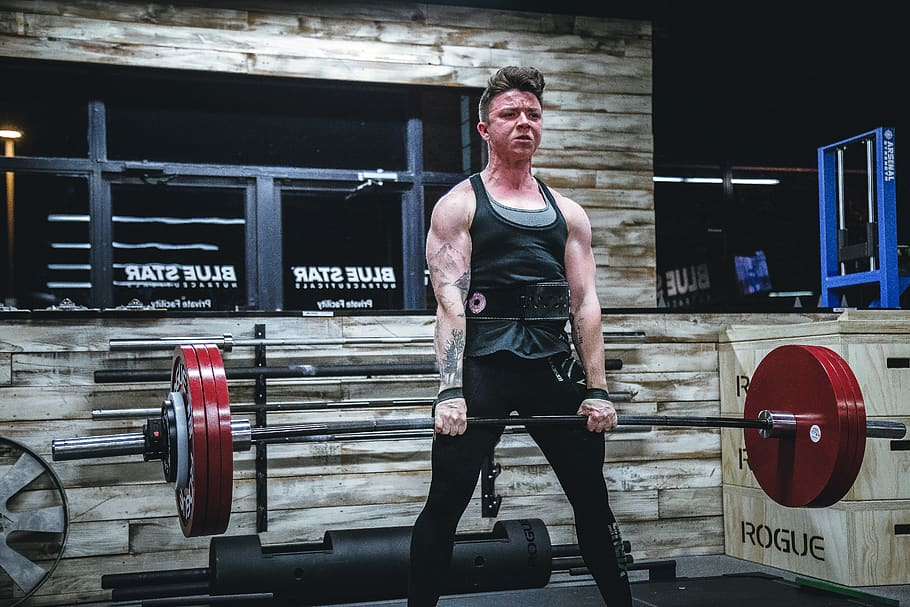 Fit man doing deadlift exercise in gym