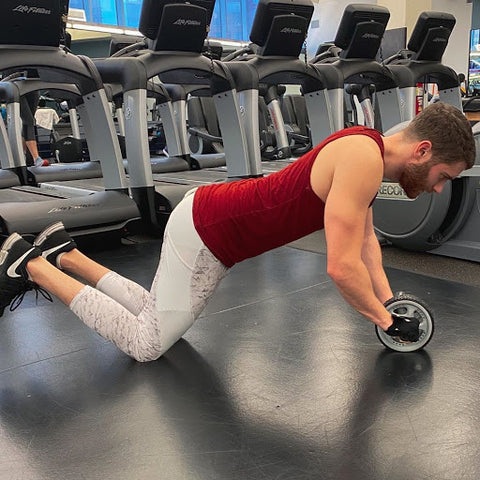man wearing white meggings using an ab wheel in the gym