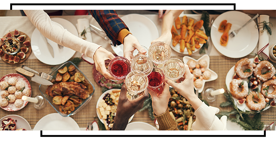 family saying cheers at a large holiday meal