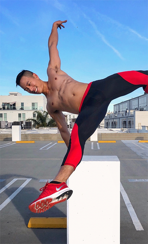 man performing parkour in red and black compression pants