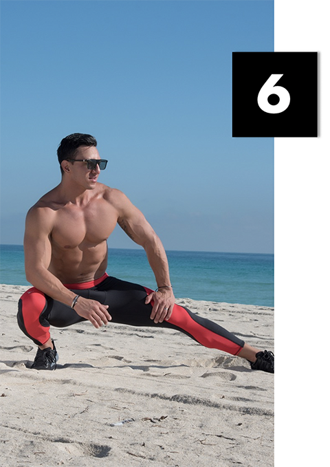 man stretching on beach in Meggings
