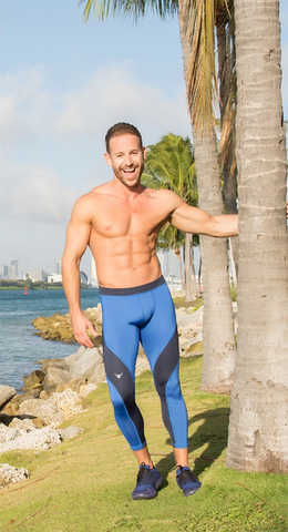 man wearing black and blue leggings by palm tree