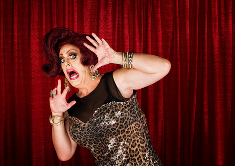 Scared drag queen with hands up in theater