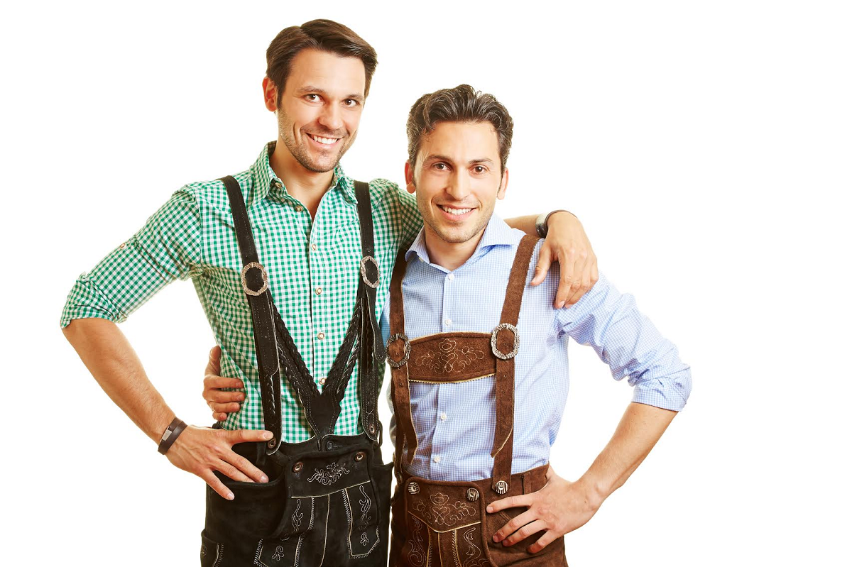 Two smiling bavarian men standing in leather pants