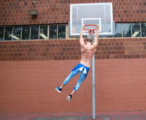 young man hanging from a basketball ring