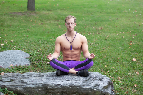 Young Man Meditating Outdoors In The Park