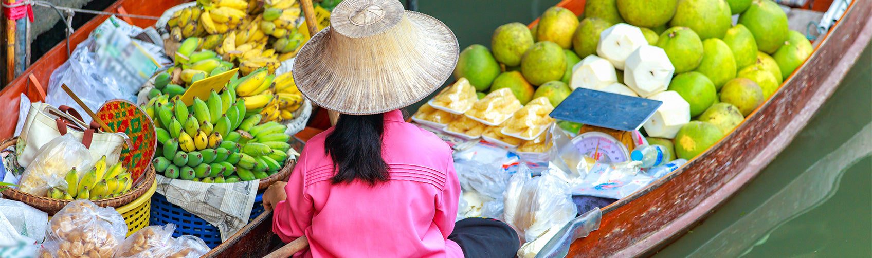 Asian woman in a selling tropical fruits from two boats