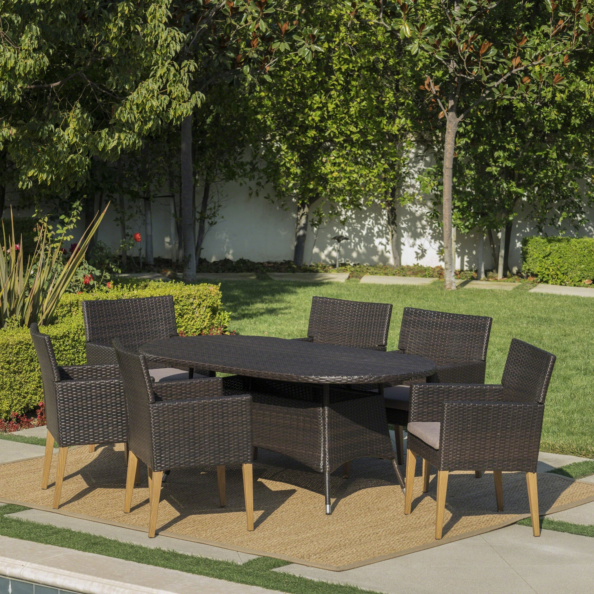 Bardow Outdoor 7 Piece Wicker Oval Dining Set With Wood Finished Legs And Water Resistant Cushions