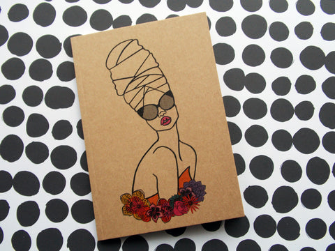 Small Kraft Notebook featuring illustration of black woman wearing headwrap surrounded by flowers illustrated by DorcasCreates