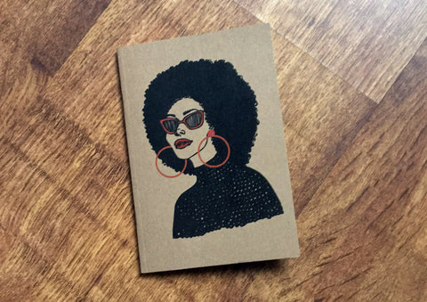 Kraft notebook featuring illustration of black woman with large afro illustrated by DorcasCreates