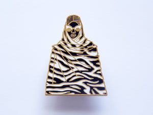 Gold and black enamel pin with tribal afrofuturist design by Dorcascreates