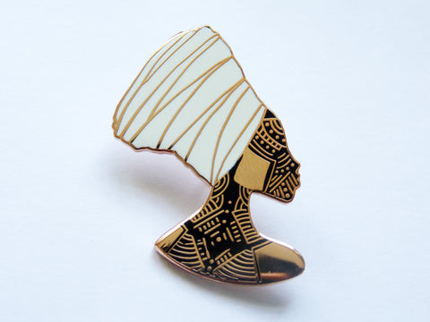 rose gold enamel pin with black filling of black woman with wearing a white headwrap with facial tribal markings by dorcascreates