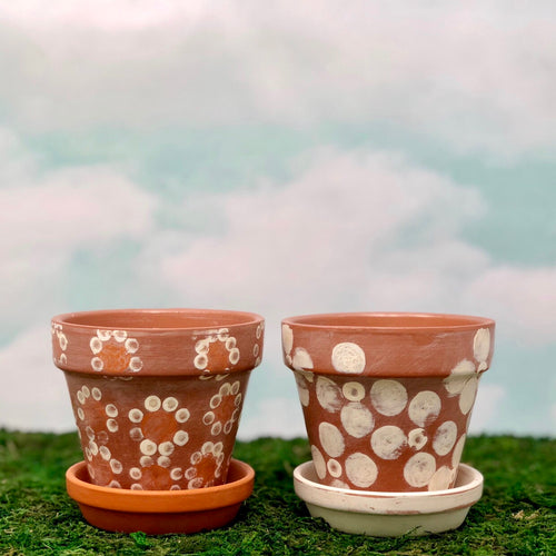 Handpainted Afrocentric Terracotta Pots with a distressed flower motif in cream and orange.