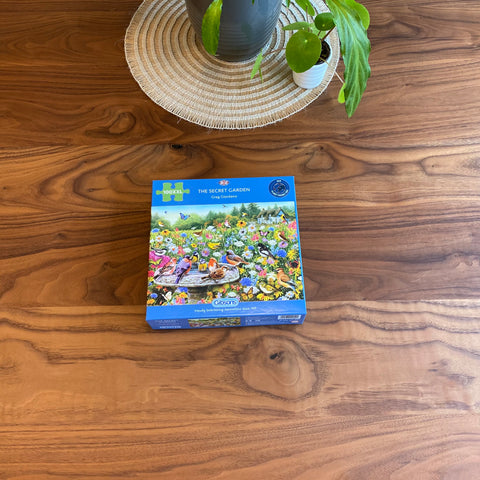 100XXL The Secret Garden jigsaw puzzle placed on a brown table with some green plants behind it.