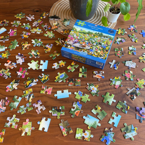 100XXL jigsaw puzzle The Secret Garden with all puzzle pieces lying on a table facing up