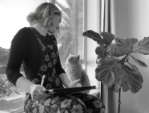 A black and white photograph of Jess looking at her cat, both sitting next to a window.